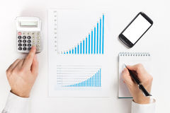 Businessman counting losses and profit working with statistics, analyzing financial the results on white background Royalty Free Stock Photography