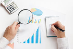 Businessman counting losses and profit working with statistics, analyzing financial the results on white background Stock Photography