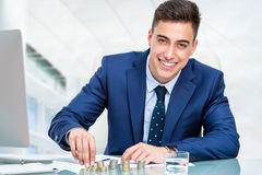 Businessman counting money at desk. Close up portrait of young accountant counting money at desk. Young businessman in blue suit sitting at desk in office Royalty Free Stock Images