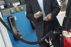 Businessman Counting Money At Fuel Station Stock Photo