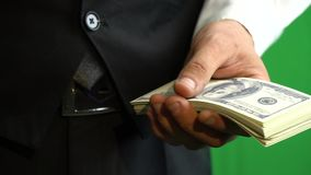 Hands of a businessman in a business suit counting one hundred dollar bills on a background of hromakey. Businessman counting money on green screen stock video