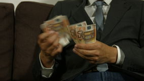 Businessman counting money and puts them in his pocket stock footage