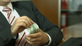 Businessman counting money and putting in pocket stock footage