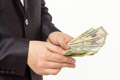 Businessman counting money on a white background Stock Images