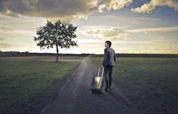 Businessman in the Countryside. Businessman with his luggage on a country road Royalty Free Stock Photos