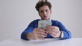 Businessman counts hundred dollar bills stock video