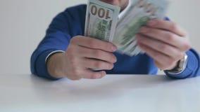 Businessman counts hundred dollar bills stock video footage