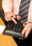 Businessman counts money on calculator Royalty Free Stock Photography