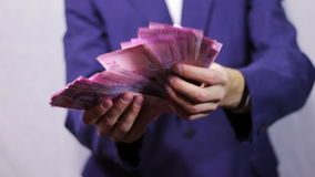 Businessman Counts Money in Hands. Businessman counts tens of thousands of Hryvnia (Ukrainian currency), holding them in their hands.  A man dressed in a stock footage