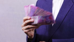 Businessman Counts Money in Hands. Businessman counts tens of thousands of Hryvnia (Ukrainian currency), holding them in their hands.  A man dressed in a stock video