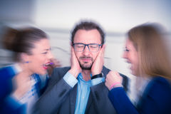 Businessman covered ears with his hands. Business women yelling. Businesspeople sitting at the office desk. Annoyed businessman covering his ears with hands and Royalty Free Stock Photo