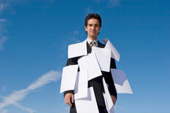 Businessman covered with papers Royalty Free Stock Image
