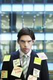 Businessman Covered With Post It Notes. Portrait of a young businessman covered with post It notes Royalty Free Stock Image