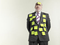 Businessman Covered With Sticky Notes. Mature businessman covered with sticky notes against gray background Stock Image