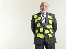 Businessman Covered With Sticky Notes. Portrait of a mature businessman covered with sticky notes against gray background Royalty Free Stock Photos