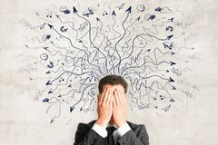 Risk and choice concept. Businessman covering face on concrete background with drawn arrows. Risk and choice concept Stock Image