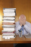 Businessman Covering Face With Hands By Stack Of Folders stock photos