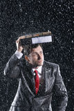 Businessman Covering Head With Binder In Rain Royalty Free Stock Photos