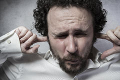 Businessman covering his ears, man in white shirt with funny exp Stock Photography