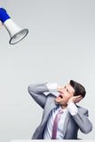 Businessman covering his ears from megaphone Stock Photography