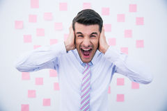 Businessman covering his ears and shouting Stock Photography