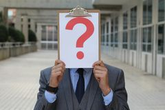 Businessman covering his face with a question mark royalty free stock photos