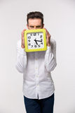 Businessman covering his face with wall clock Royalty Free Stock Images