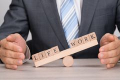 Businessman covering imbalance between life and work on seesaw. Midsection of businessman covering imbalance between Life and Work on seesaw at table stock photos