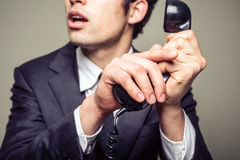 Businessman covering the phone. Businessman is covering the phone to speak in private to someone in the room Royalty Free Stock Photo