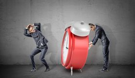 A businessman covers his head form a giant red retro alarm clock being winded up by another businessman. Time bomb. Strict deadline. Teamwork rules Royalty Free Stock Image