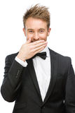 Businessman covers mouth with hand Stock Photo