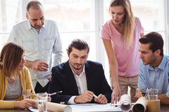 Businessman with coworkers looking at blueprint Royalty Free Stock Photography
