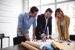 Businessman with coworkers looking at blueprint Stock Photo