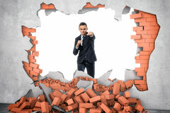 Businessman crashed wall by his hand. A businessman standing near the hole in the wall which he has just made with a hard punch, a pile of red bricks are lying Royalty Free Stock Photo