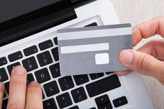 Businessman with credit card shopping online at desk Stock Photos