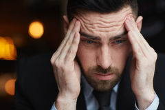 Businessman in Crisis. Portrait of frustrated bearded businessman rubbing his temples ooking stressed and troubled against black background Stock Photo