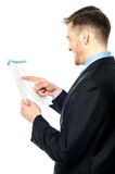 Businessman cross-checking annual reports Royalty Free Stock Photo