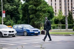 Businessman cross the street outdoor with briefcase wearing a gas mask stock images