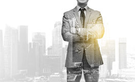 Businessman with crossed arms over city buildings. Business, people and corporate concept - handsome businessman with crossed arms over over city skyscrapers Stock Images