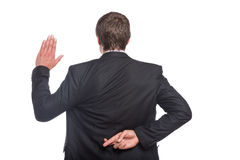 Businessman with crossed fingers and stop gesture. Rear view of a businessman with crossed fingers and stop gesture over white background Royalty Free Stock Images