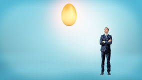 A businessman with crossed hands looks up to a large shining golden egg overhead. Stock Photos