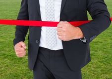 Businessman crossing finish line against green grass Royalty Free Stock Photography
