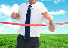 Businessman crossing finish line against sky and cloud Royalty Free Stock Photos