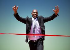 Businessman crossing finish line with arms up royalty free stock image