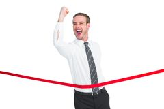 Businessman crossing the finish line while clenching fist Stock Photos