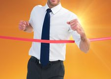 Businessman crossing finish line at dusk Royalty Free Stock Photography