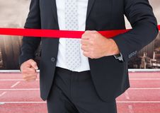 Businessman crossing the finish line in ground Stock Photos