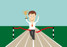 Businessman crossing finish line with trophy cup. Excited businessman crossing finish line with trophy cup in hand, for business competition or success concept Royalty Free Stock Photography