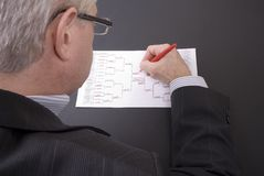 March Madness Businessman Crossing Out Teams on Bracket Royalty Free Stock Photos
