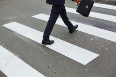 Businessman crossing road Stock Images